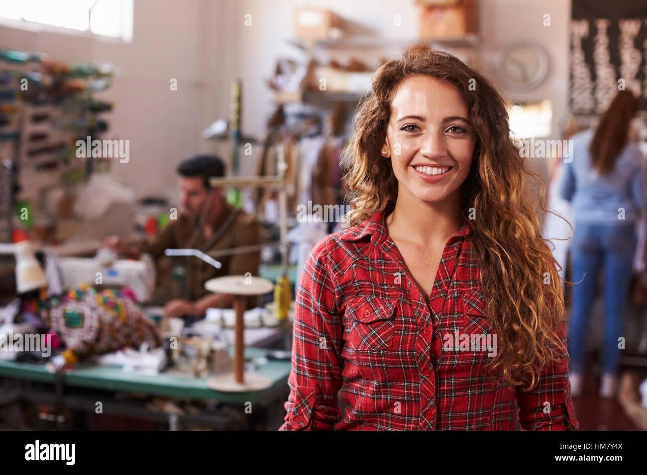 Long haired white female clothes designer in design studio - Stock Image