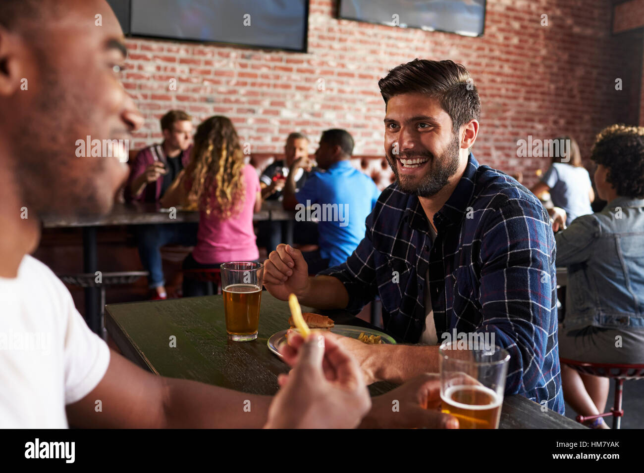 Friends Eating Out In Sports Bar With Screens In Background - Stock Image
