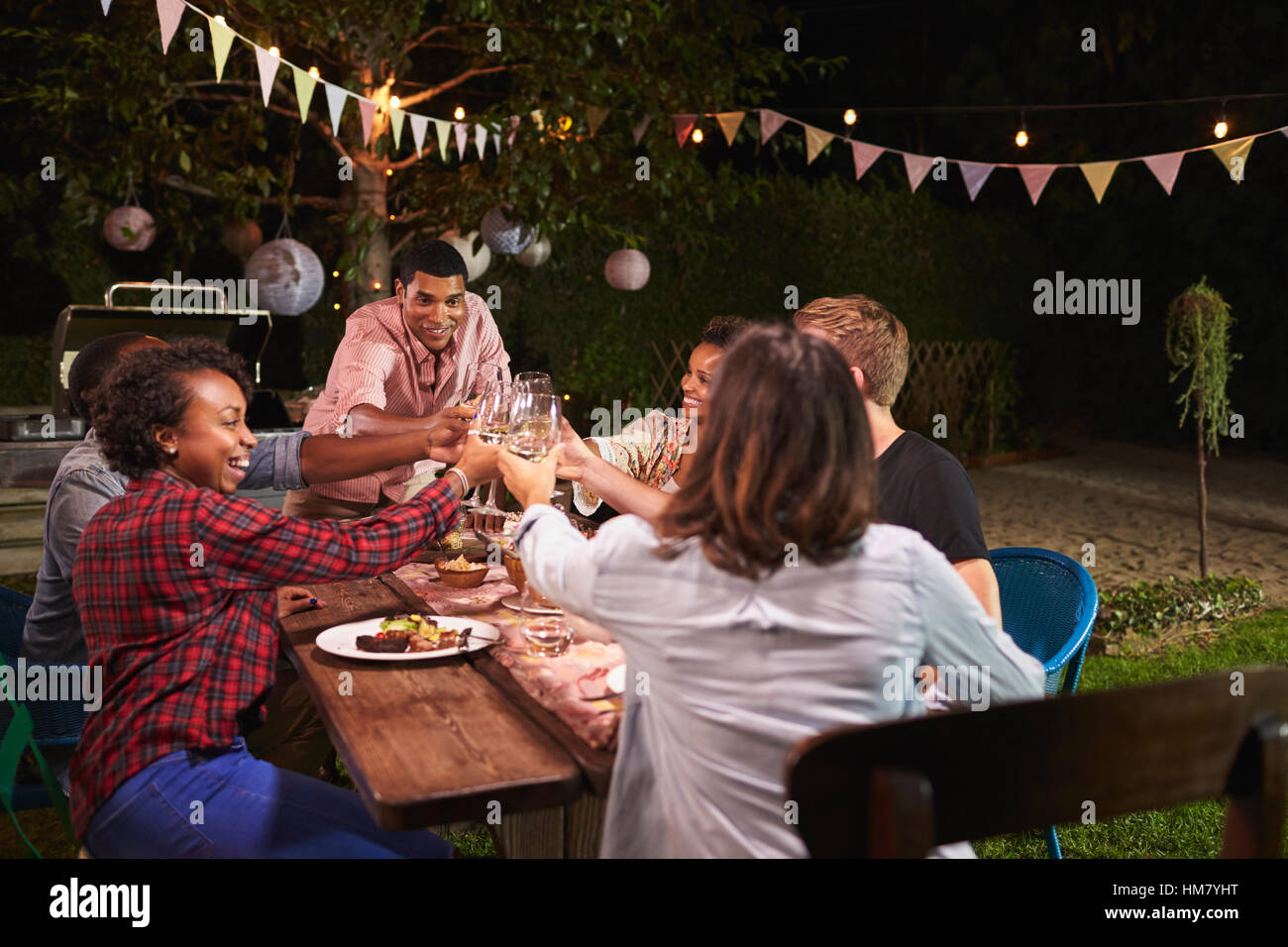 Friends and family making a toast at dinner party in garden - Stock Image