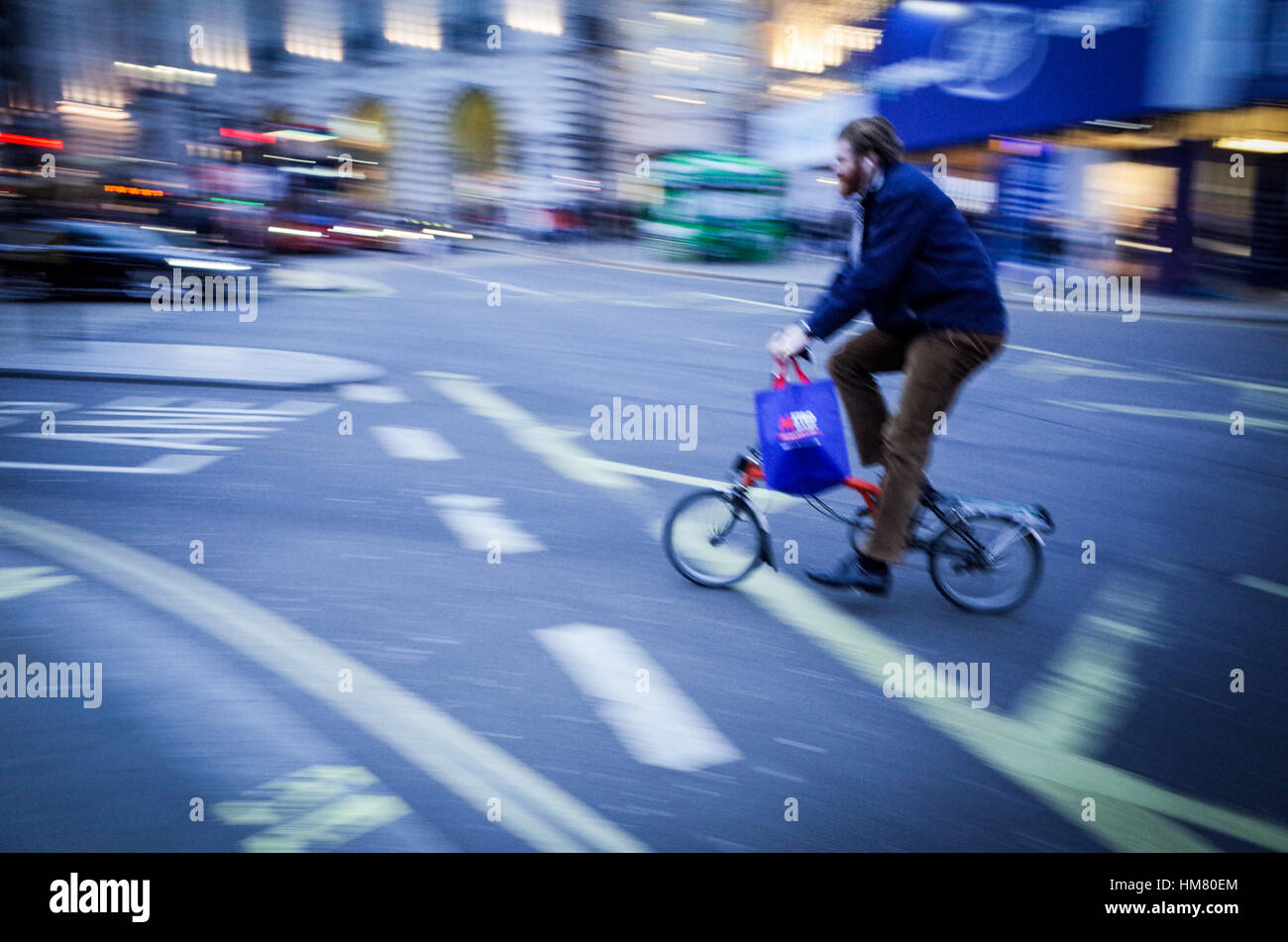 A cyclist on a Brompton folding bike crosses Piccadilly Circus in Central London - motion blur - Stock Image