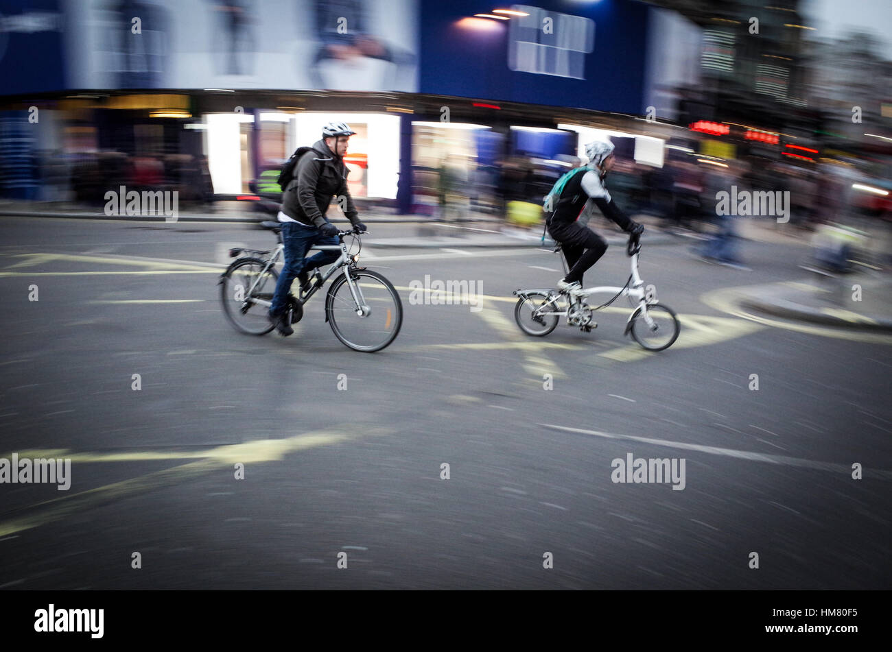 Two cyclists commute across the Piccadilly Circus in central London - Motion Blur - Stock Image