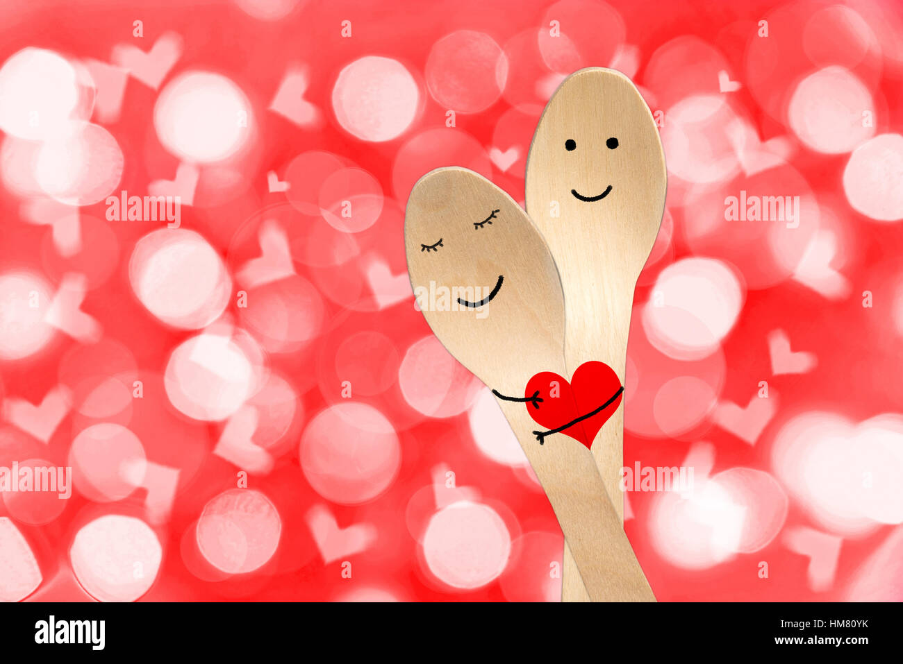 Happy couple hug concept, smiley painted on spoons, valentines day background - Stock Image