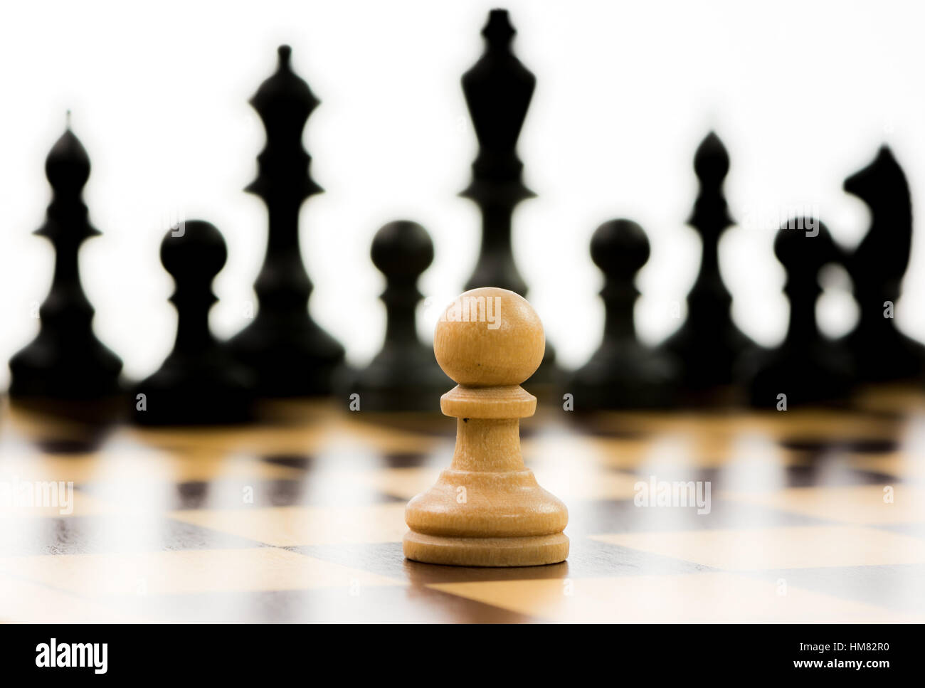White pawn against a superiority of black chess pieces on a chess board. Selective focus. - Stock Image