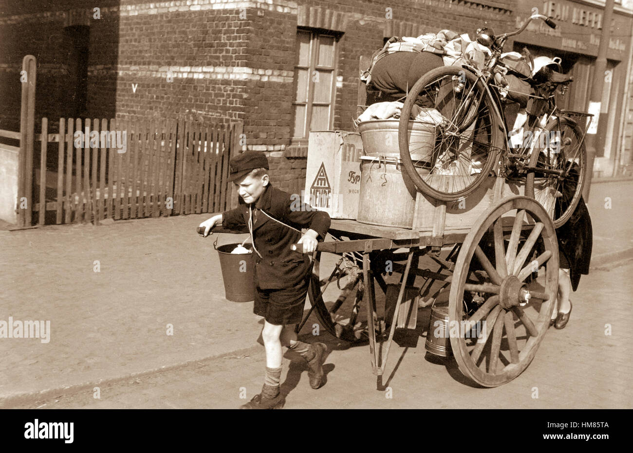 Lad with mother pushing from behind rolls cartload of possessions out of Uerdingen, Germany, moved out by allied - Stock Image