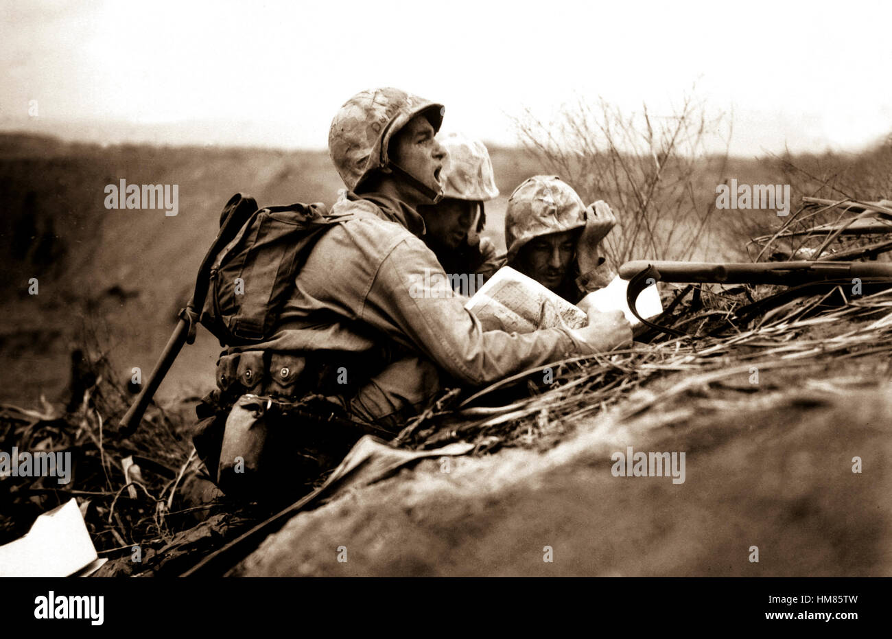 Observer who spotted a machine gun nest finds its location on a map so they can send the information to artillery - Stock Image