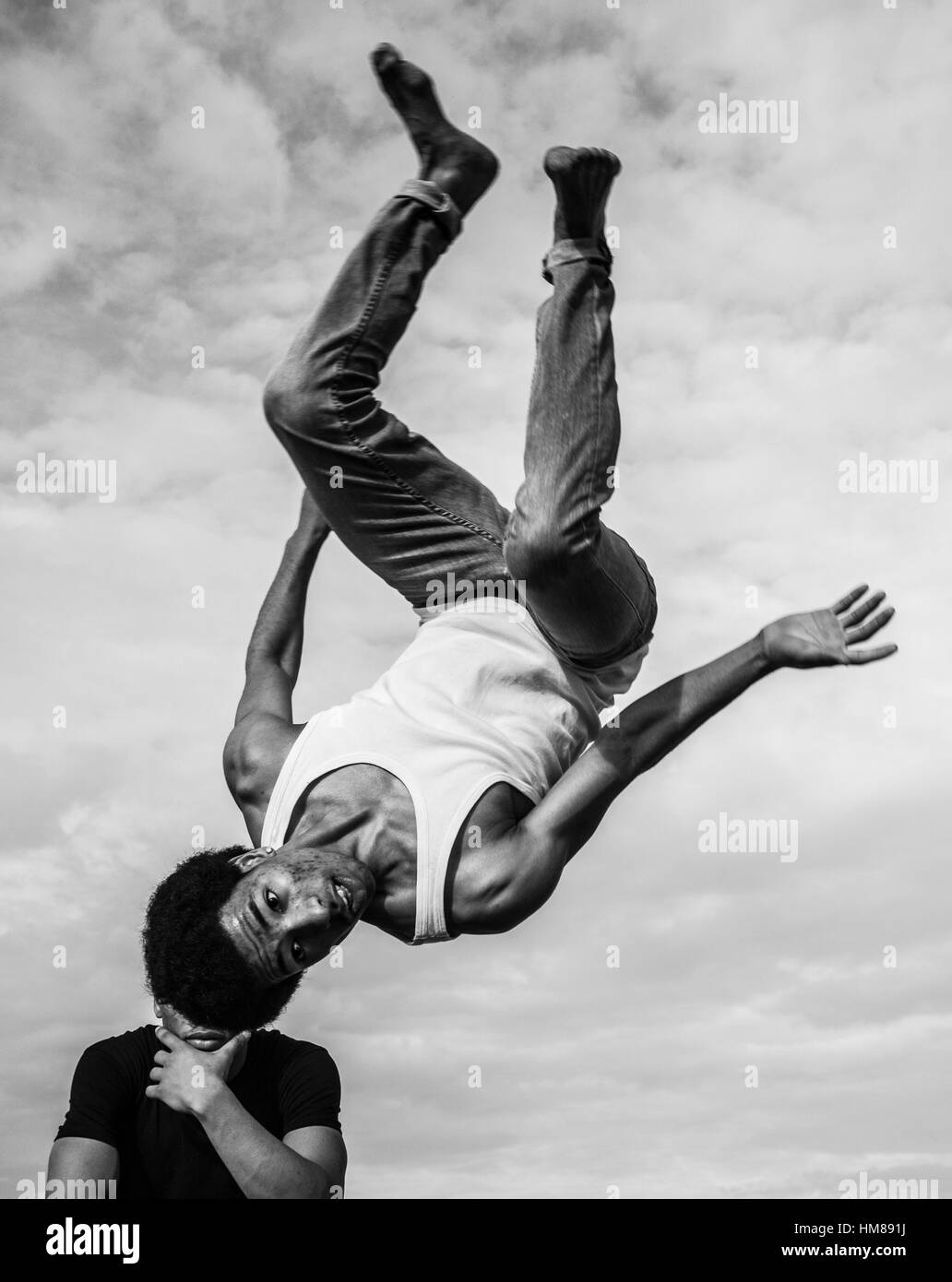 Young Adult Man Flipping Upside Down in Air - Stock Image