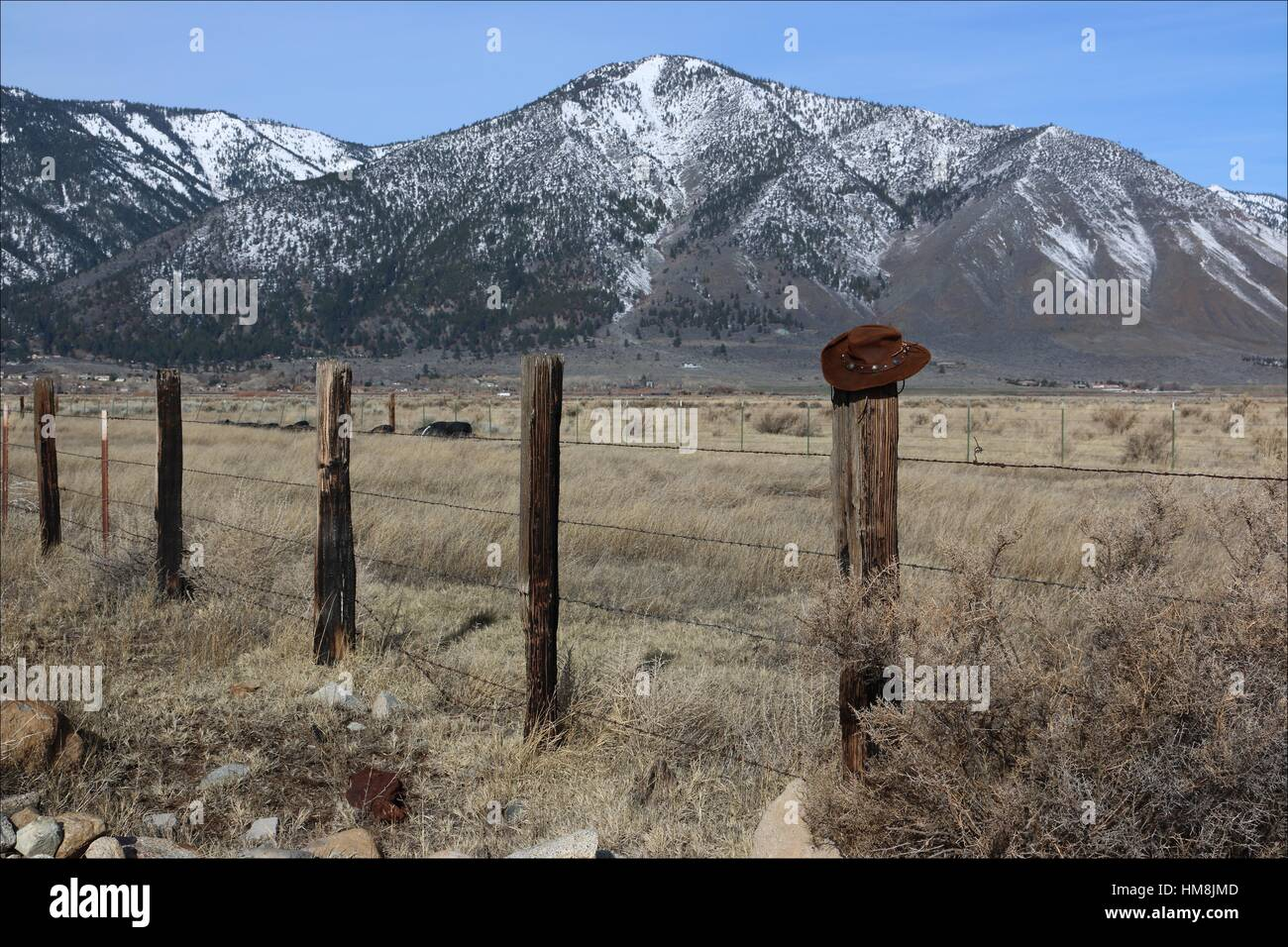 A Cowboy Hat Sits Atop An Old Fence Post, Set Against A Background Of The  Eastern Side Of The Sierra Nevada Mountains In Genoa, Nevada, USA
