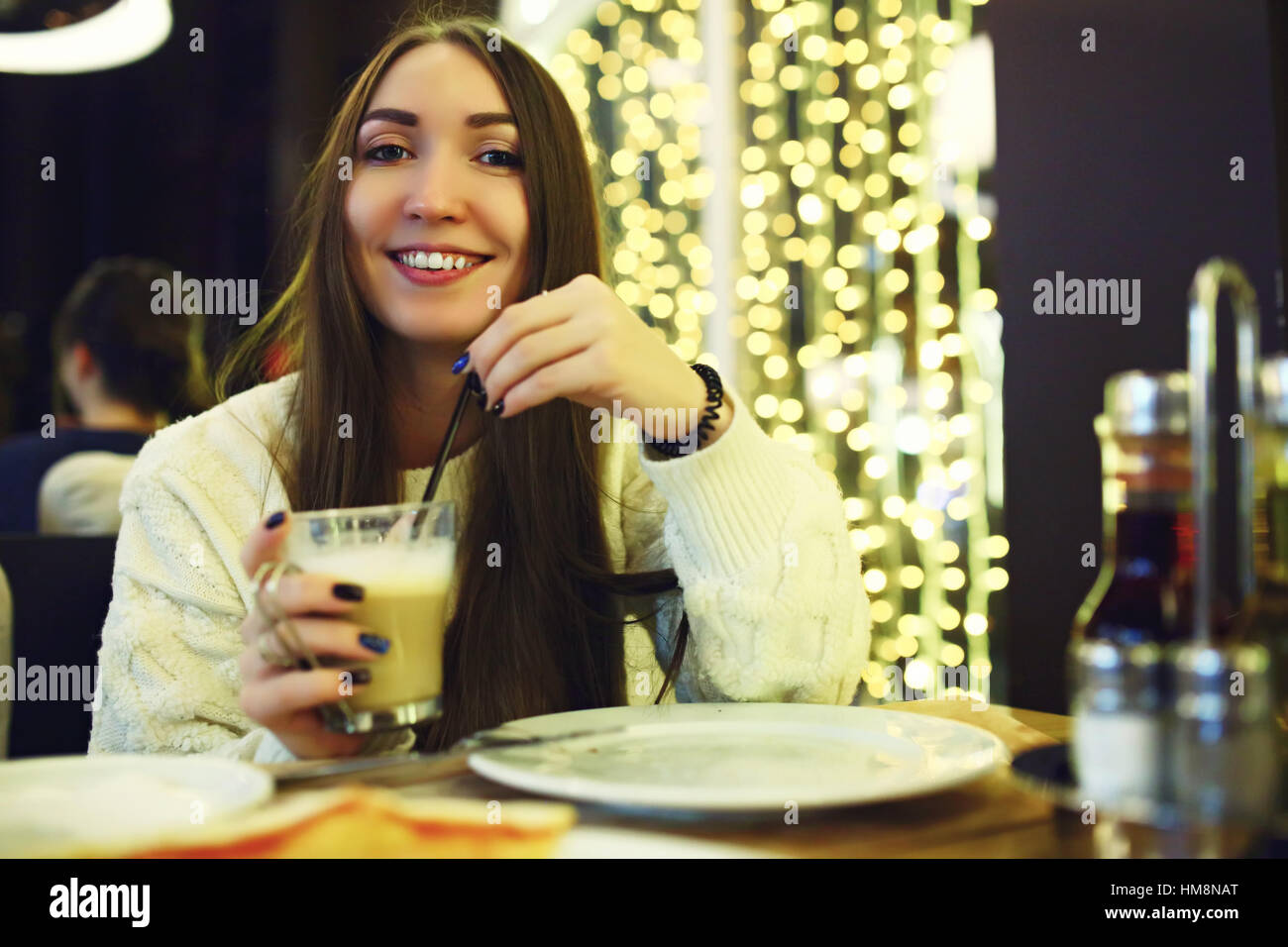 Beautiful young woman drinking coffee at cafe. Tonned. Selective focus. - Stock Image