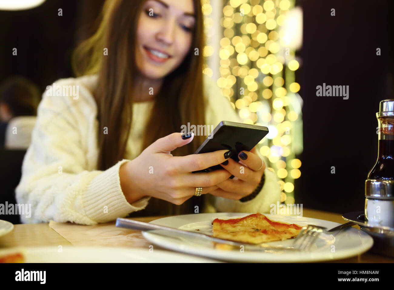 Woman typing write message on smart phone in a modern cafe. Cropped image of young pretty girl sitting at a table - Stock Image