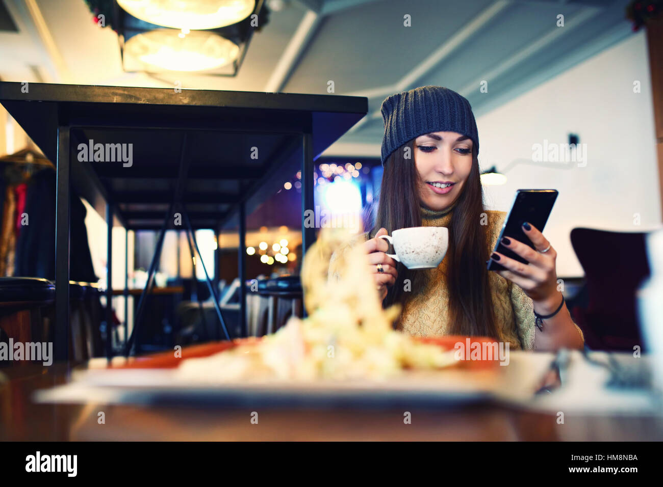 Portret of young female reading sms on the phone in cafe. Tonned. Selective focus. - Stock Image