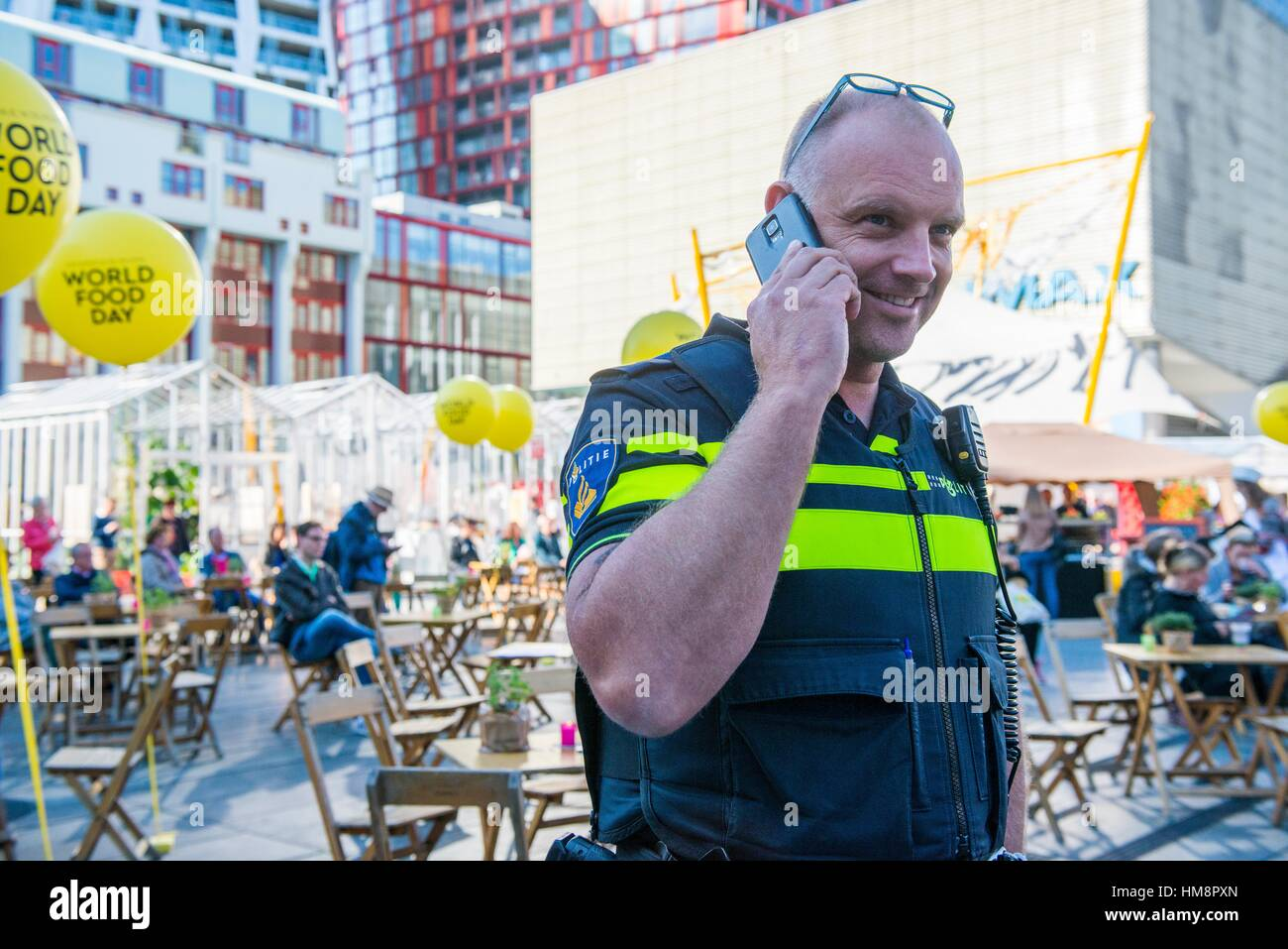 Rotterdam, Netherlands. Senior adult policeman making a phone call with his colleagues at the police station during - Stock Image