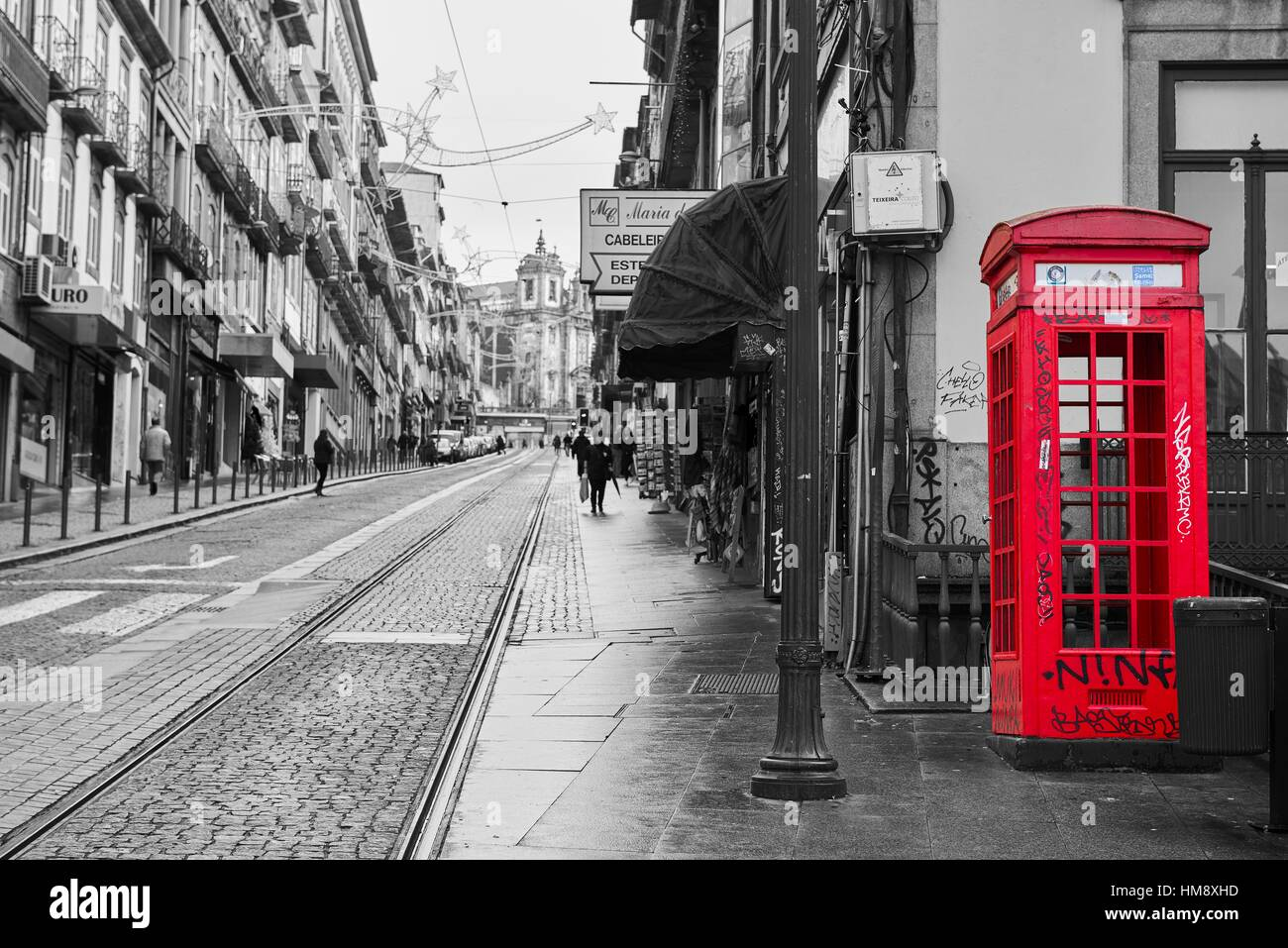 Photograph in black and white mixed with colour of the red telephone box in porto portugal europe
