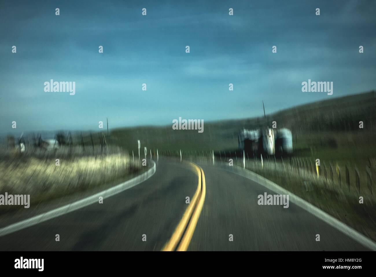 A two lane road passes through pastureland in rural California. - Stock Image