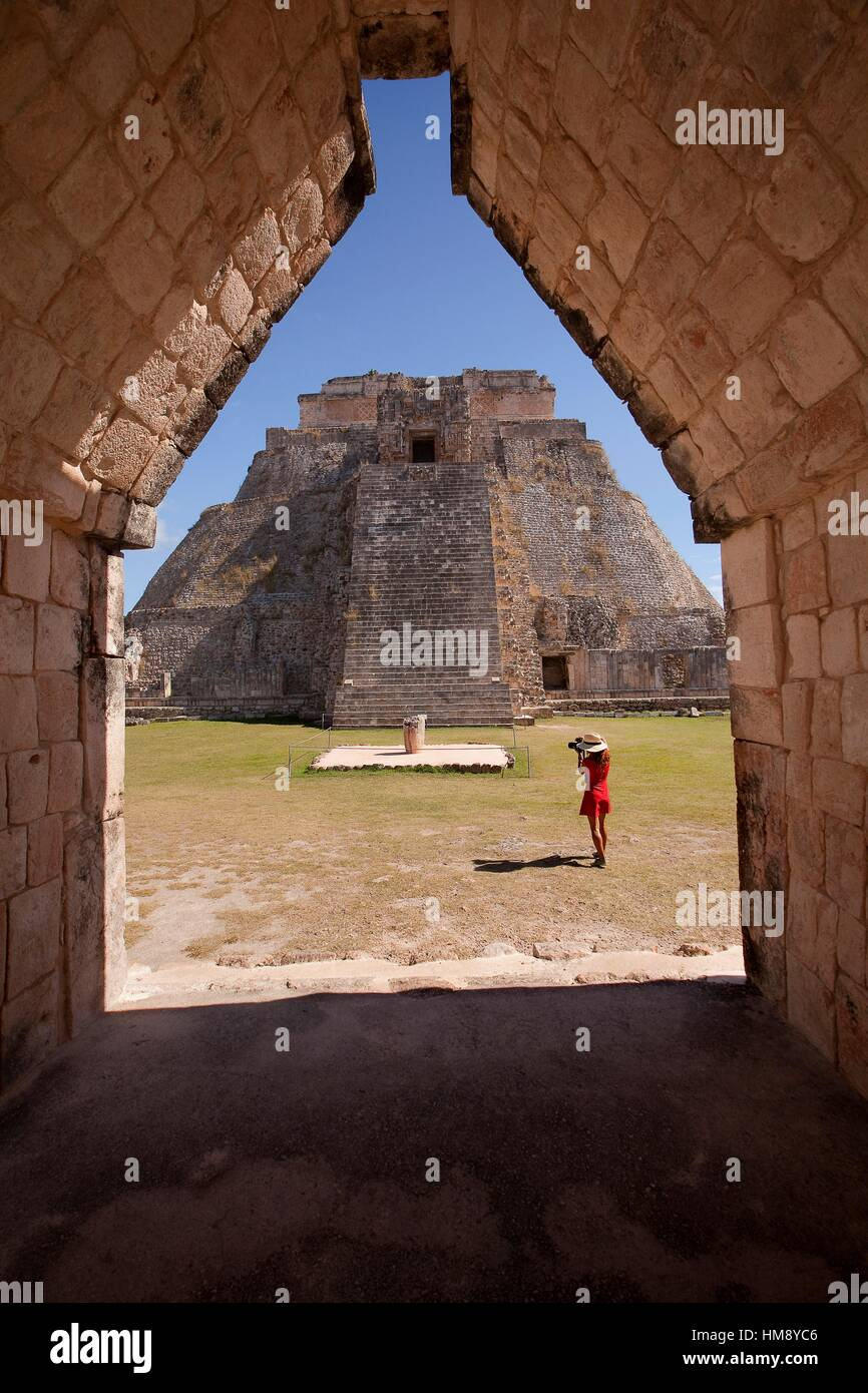 Tourist taking photos of the the Pyramid of the Magician, Maya archeological site Uxmal, Yucatan, Mexico, Central - Stock Image