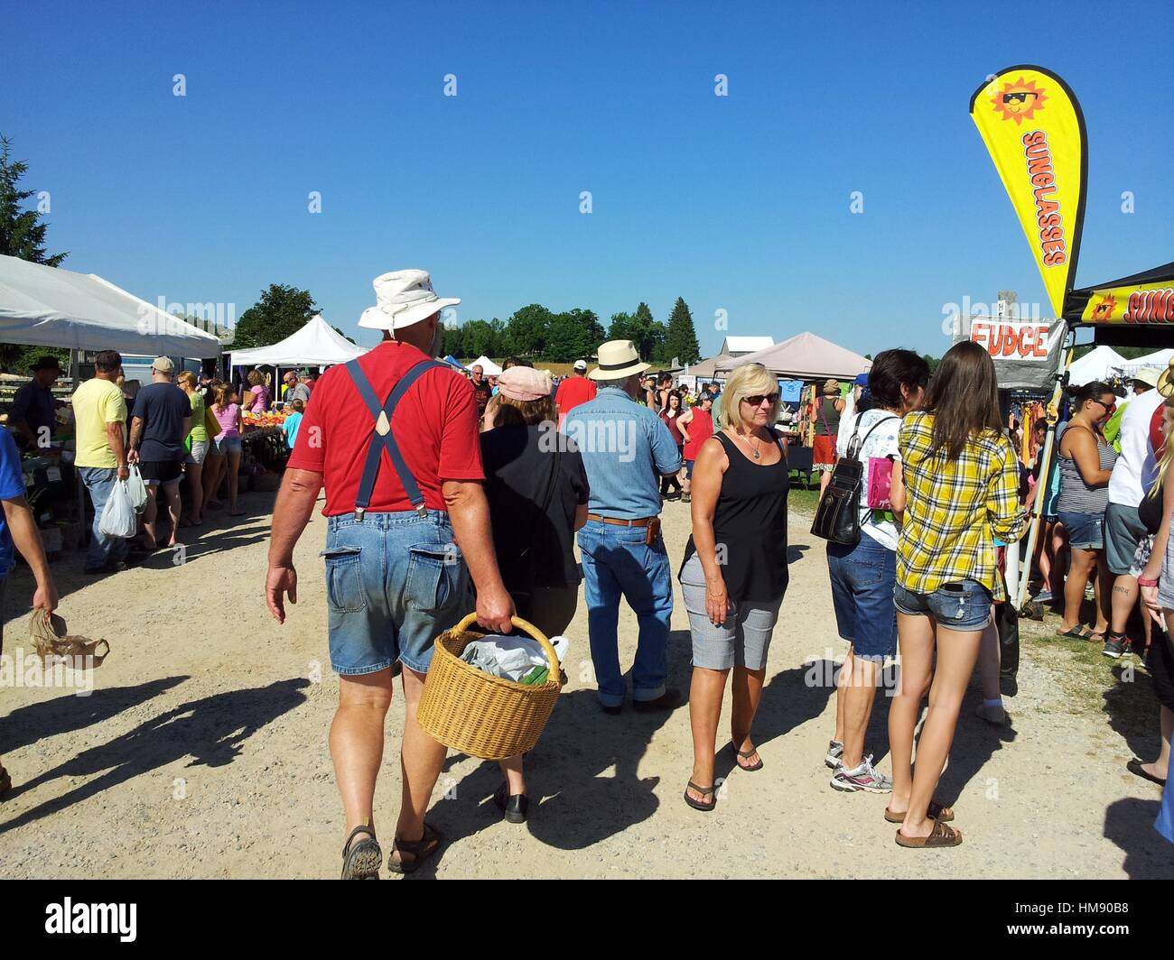 A man with suspenders, a red shirt and short pants carries a basket through a crowd of people at a weekly market Stock Photo