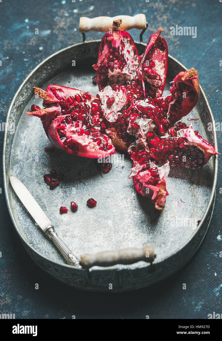 Fresh ripe pomegranate broken in pieces in metal tray - Stock Image