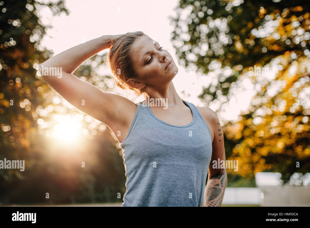 Portrait of healthy young woman stretching her neck outdoors. Caucasian fitness model warming up in park. - Stock Image
