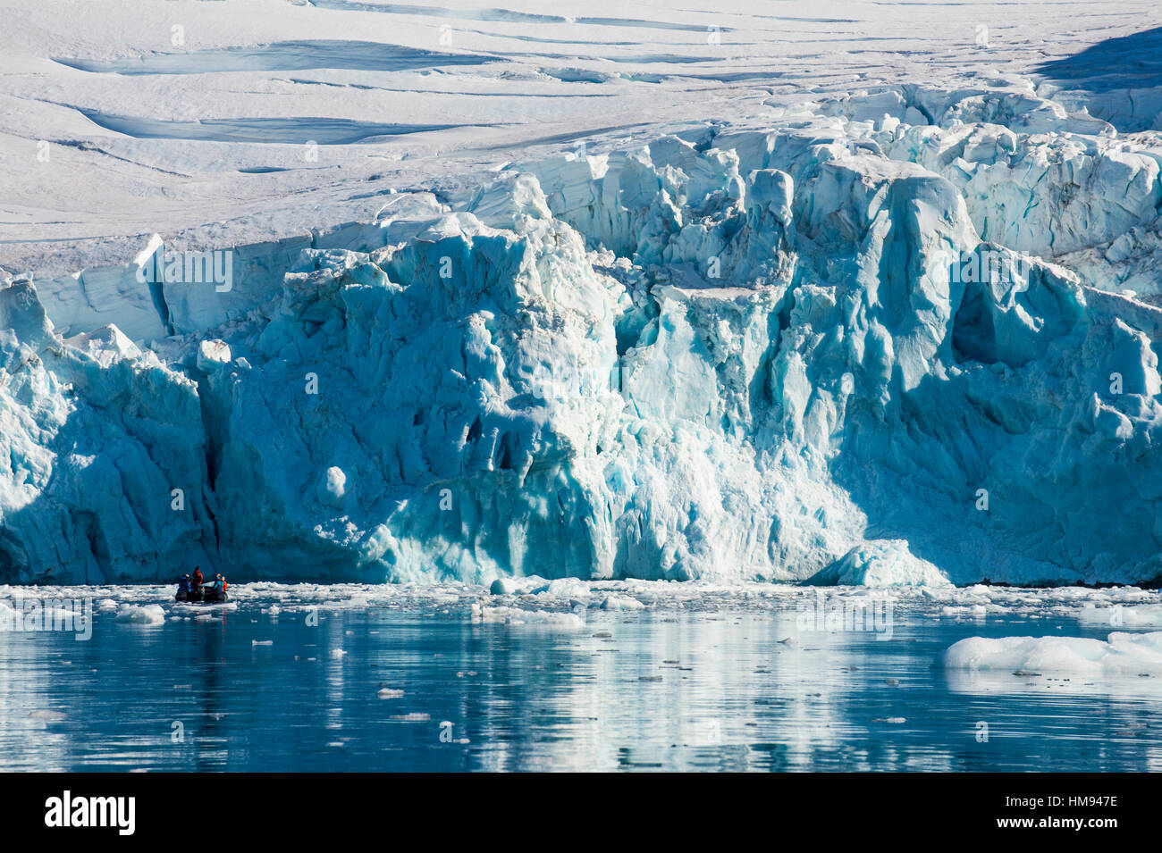 Zodiac with tourists cruising in front of a huge glacier, Hope Bay, Antarctica, Polar Regions - Stock Image