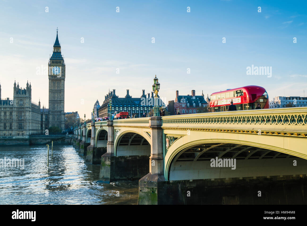 Red bus crossing Westminster Bridge towards Big Ben and the Houses of Parliament, London, England, United Kingdom - Stock Image