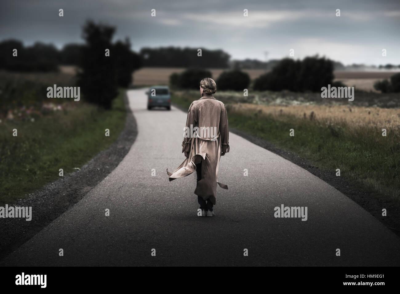 backside of woman with long overcoat walking on narrow road - Stock Image
