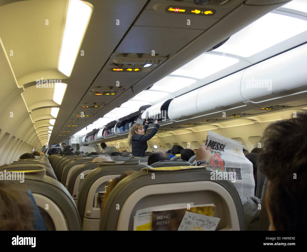 Aircraft interior scene, Barcelona airport, Vueling Airline flight departure boarding Stewardess carry-on luggage - Stock Image