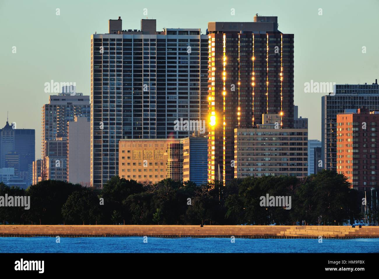 The sun reflects on windows and balconies on a high rise condominium overlooking Chicago's Montrose Harbor and - Stock Image