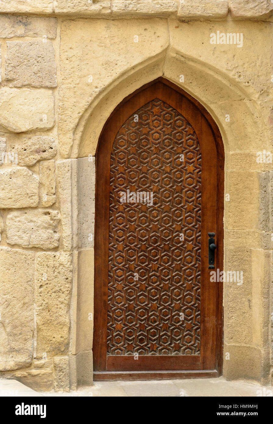 Traditional wooden door with curved arch in Old city, Icheri Sheher is the historical core of Baku. Azerbaijan. - Stock Image