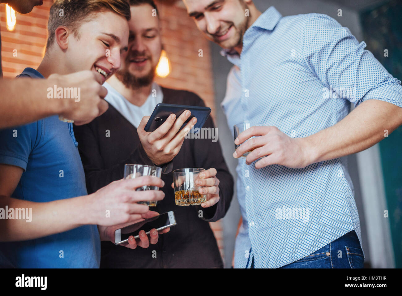 Cheerful old friends communicate with each other and phone watch,  glasses of whiskey in pub. Concept  entertainment - Stock Image