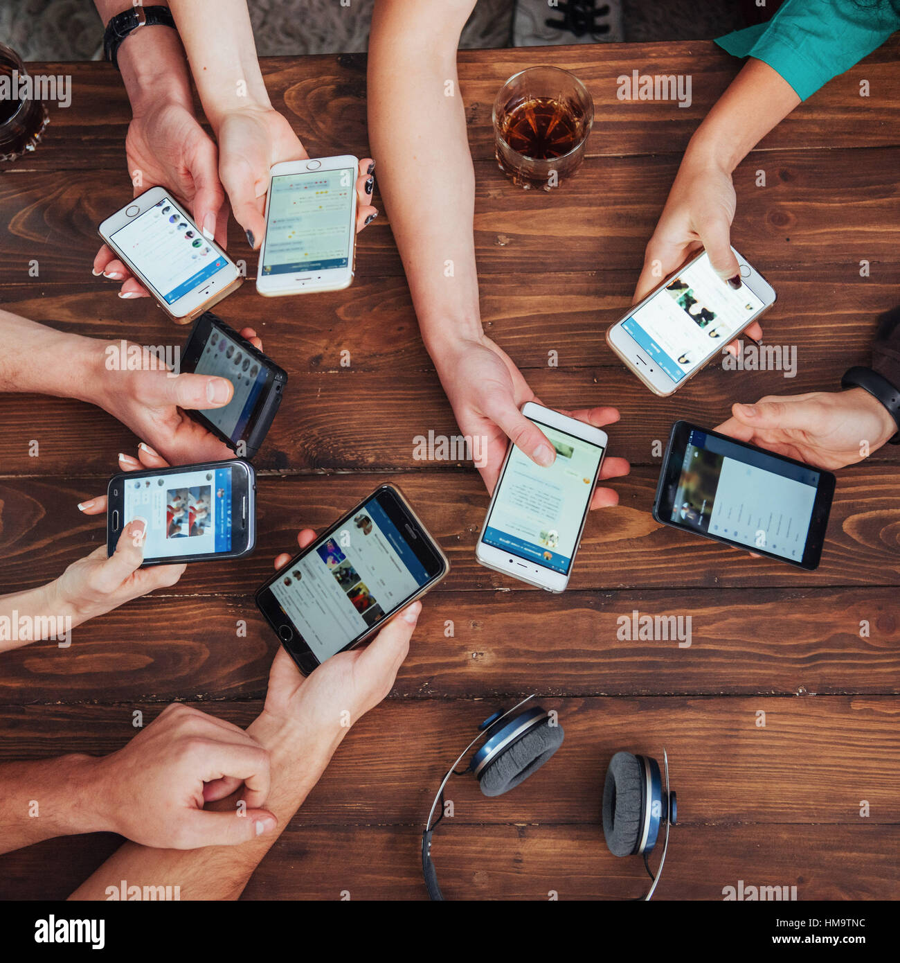 Top view hands circle using phone in cafe - Multiracial friends mobile addicted interior scene from above - Wifi - Stock Image