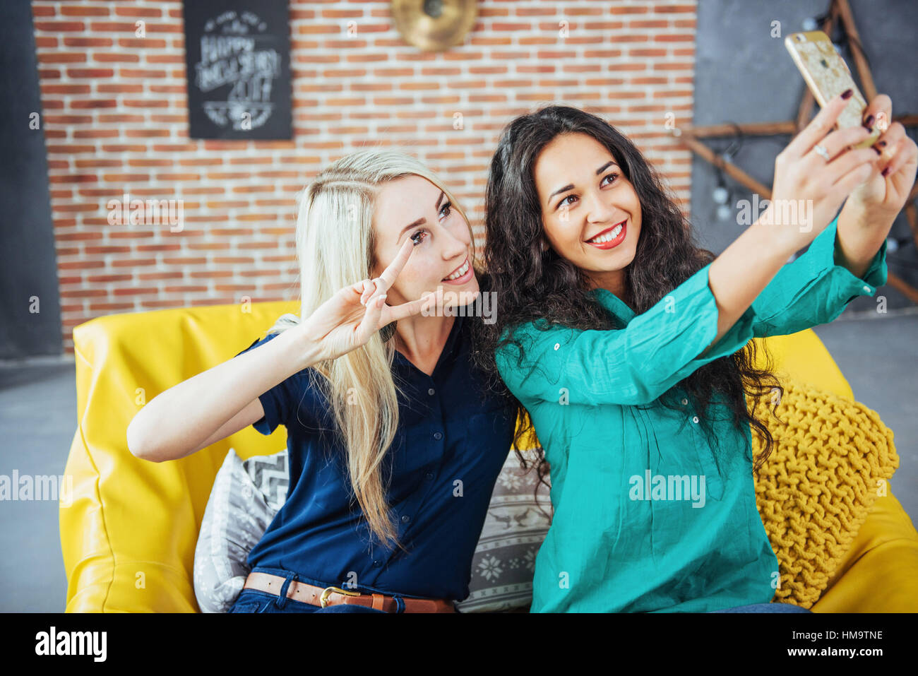 Two beautiful young woman doing selfie in a cafe, best friends girls together having fun, posing emotional lifestyle - Stock Image