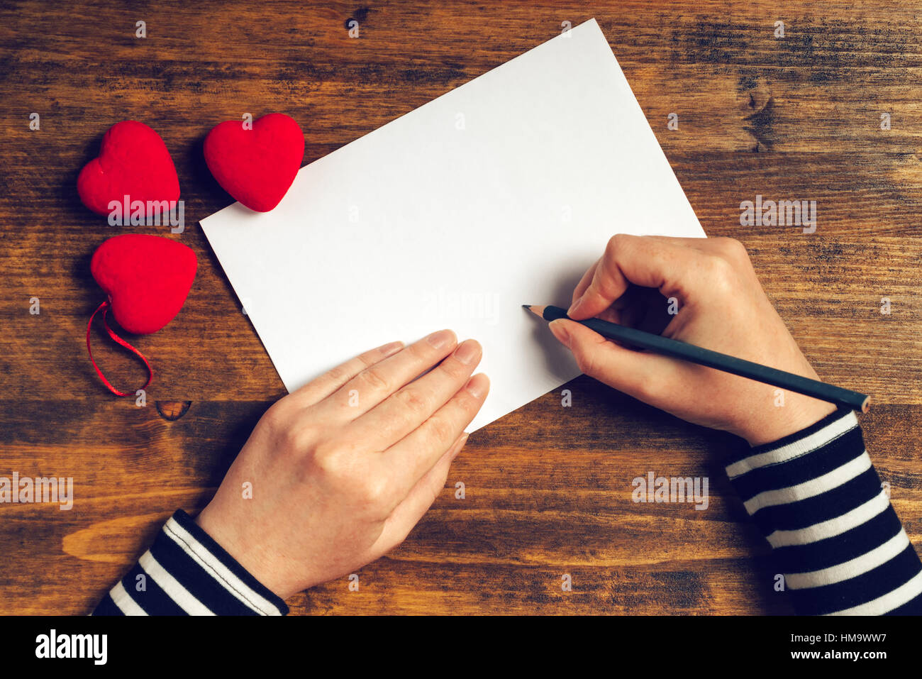 Woman writing love letter or romantic poem for Valentines day, top view of female hands - Stock Image