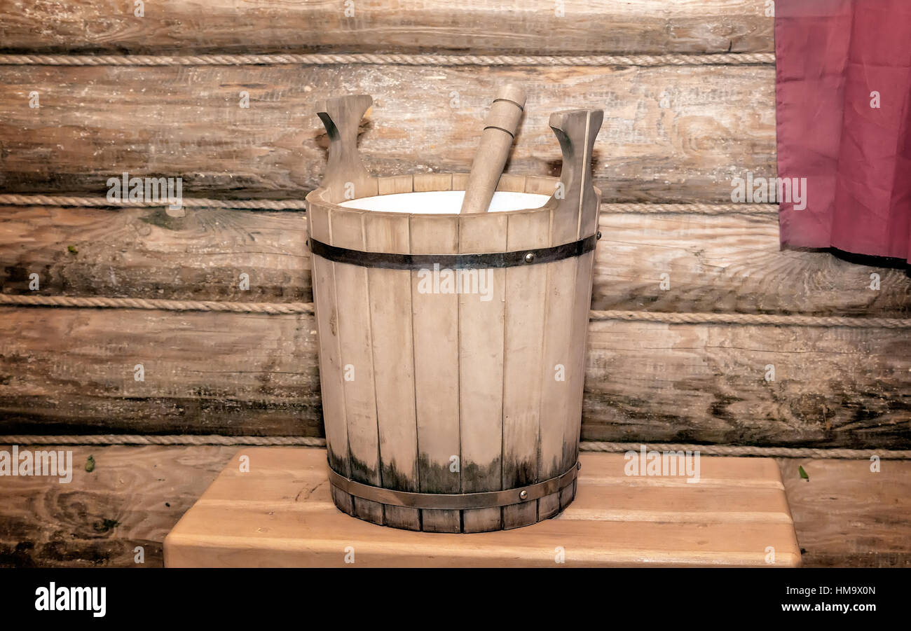 The interior of a small bath with wooden walls. On the bench a barrel made of oak planks for the water. - Stock Image