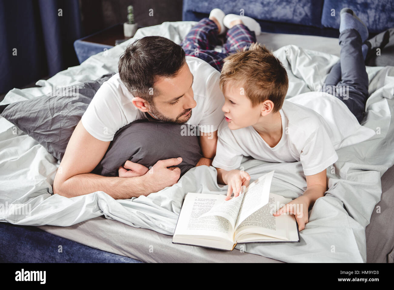Father and son reading book - Stock Image
