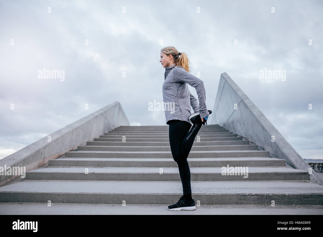 Side view of young female stretching her leg. Fitness woman warming up before jogging. - Stock Image