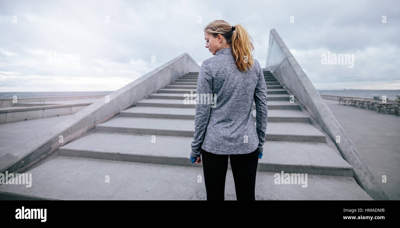 Rear view shot of young female standing by a stairs before workout. Fitness female model standing by steps in morning. - Stock Image