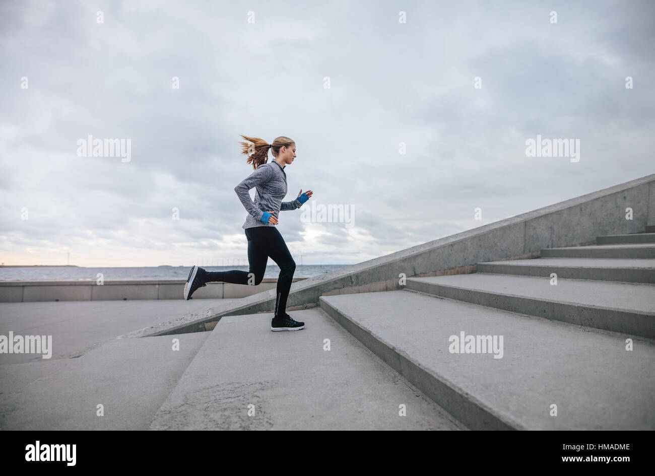 Side view shot of fitness woman running up on steps. Female runner athlete going up stairs. - Stock Image