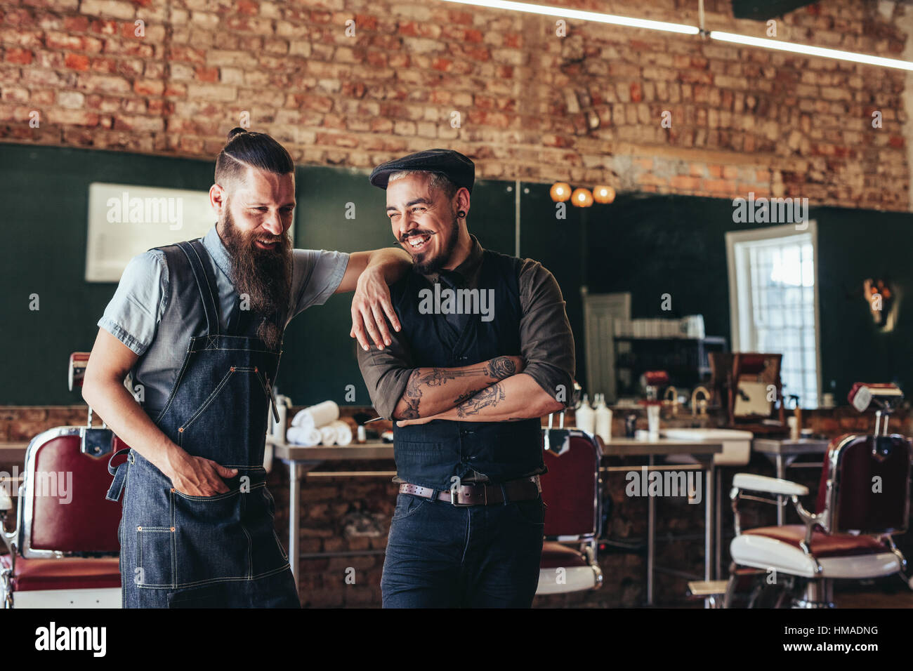 Shot of hairdresser with a man standing at barbershop. Hairstylist and client at salon - Stock Image