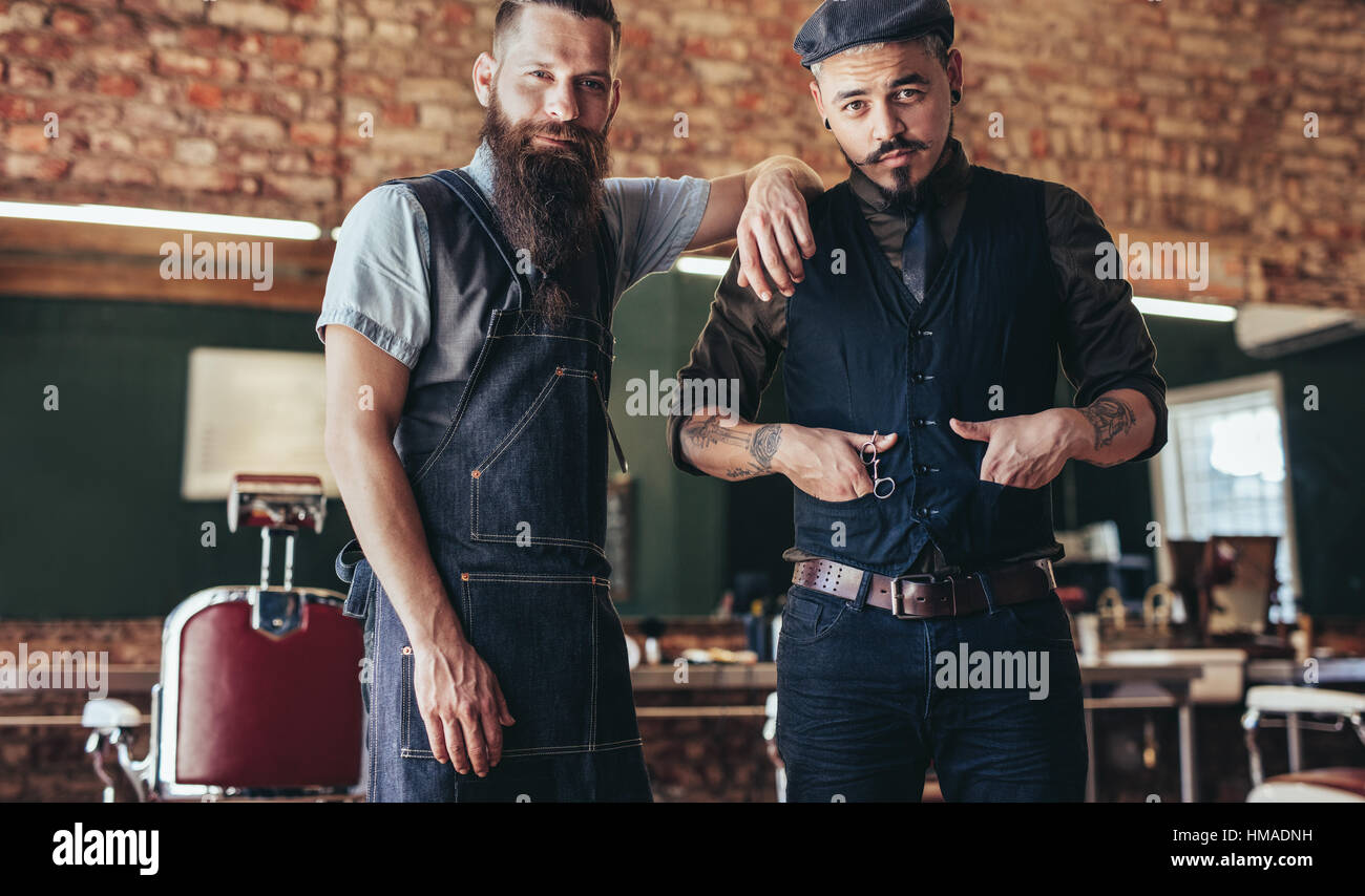 Shot of barber with stylish young man standing at salon. Two men standing at barber shop. - Stock Image