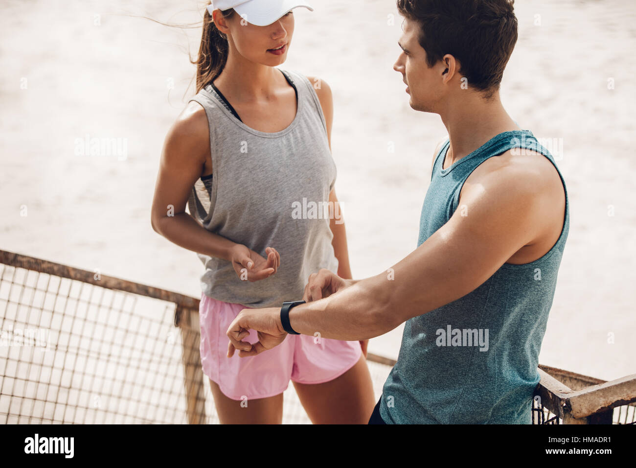 Young couple discussing training performance during workout break outdoors. Runners with heart rate monitor on the - Stock Image