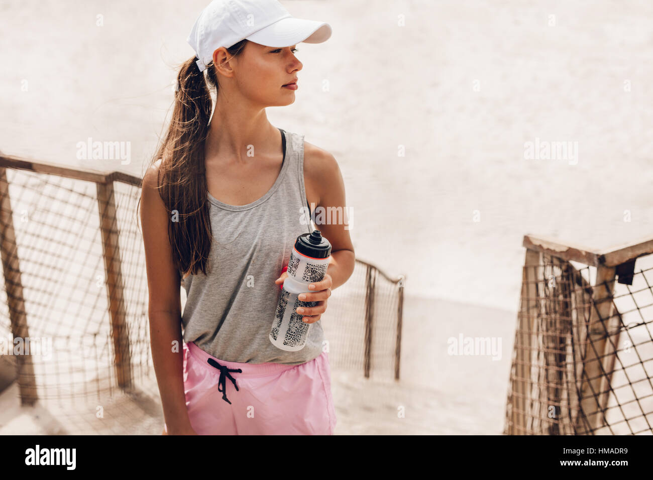 Shot of beautiful young woman at the beach taking a break. Fitness female with water bottle taking a break after - Stock Image