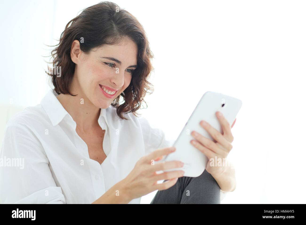 Woman using tablet computer and smiling - Stock Image