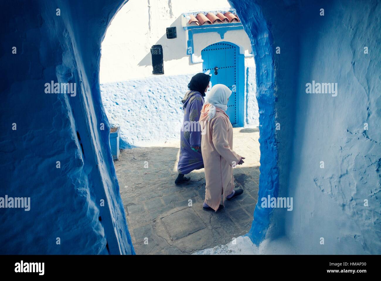 Two women with djellabas and hijabs walking, viewed through an archway. Chaouen, Morocco - Stock Image