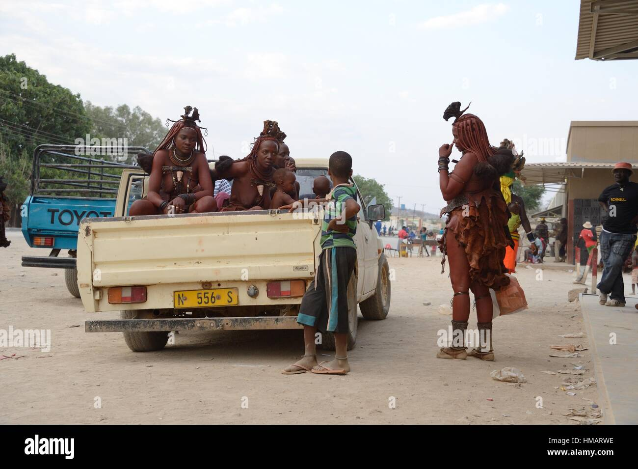 Himba women leaving the market in their car. Women always sit in the open cargo area of the pick-up since they are - Stock Image