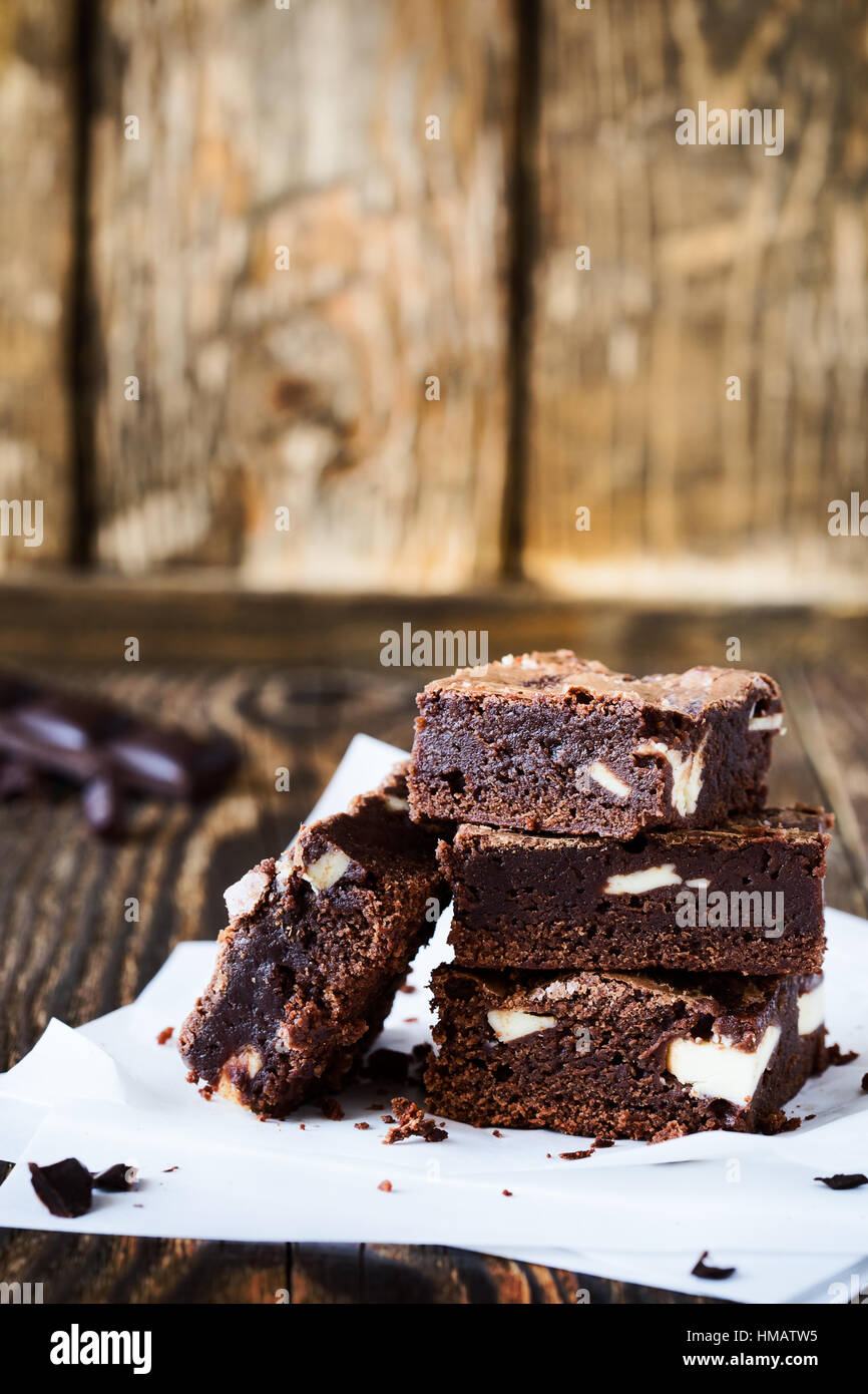 Homemade chocolate brownies with cream cheese on baking paper on rustic wooden table - Stock Image