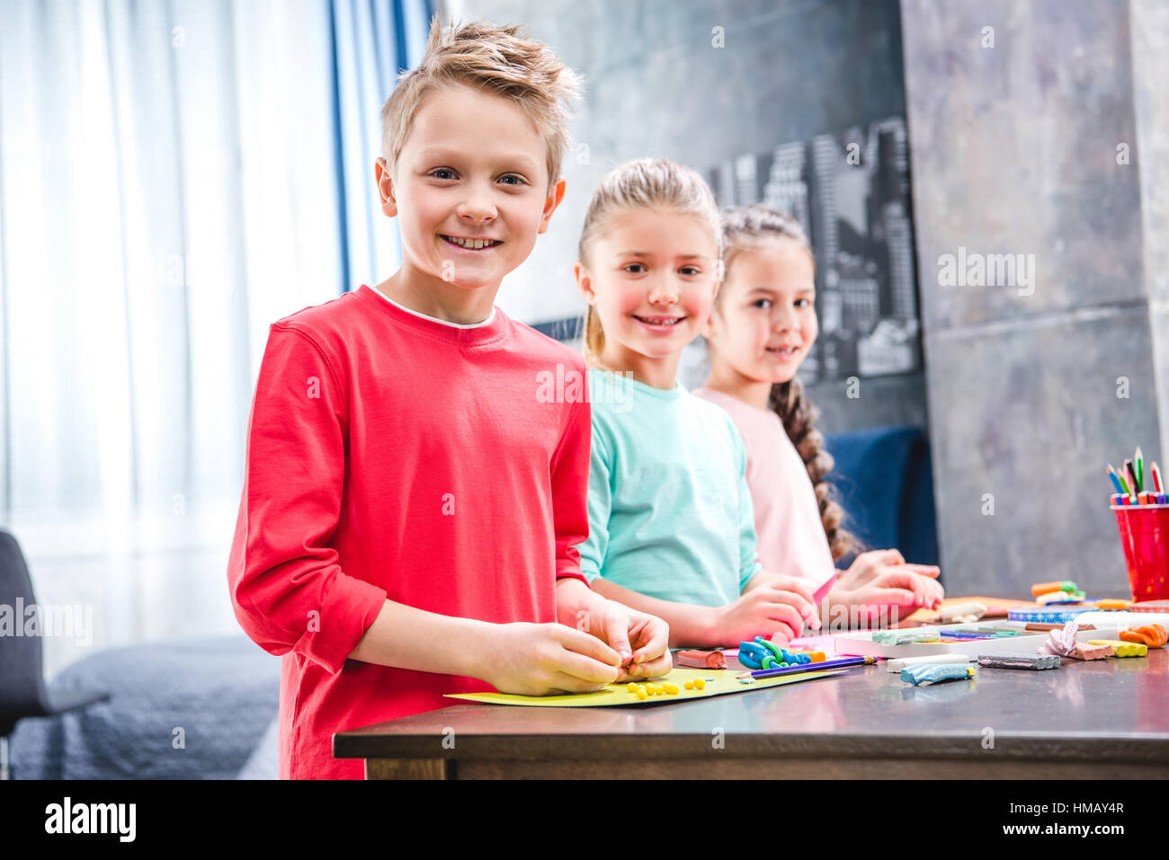Schoolchildren playing with plasticine - Stock Image