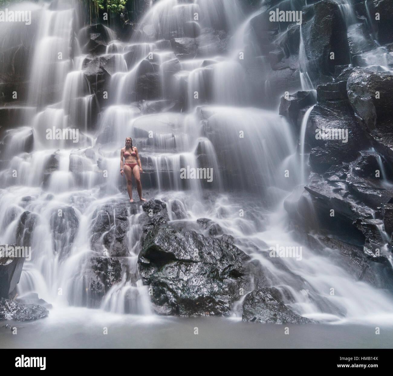 Woman standing in waterfall, Air Terjun Kanto Lampo, near Ubud, Bali, Indonesia - Stock Image