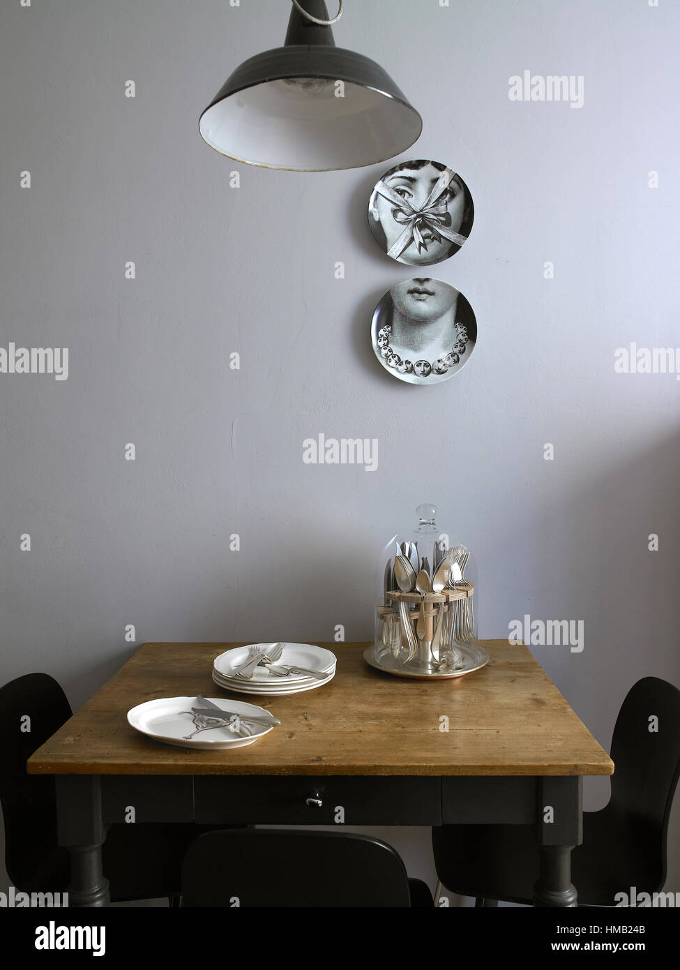 Interior of a house,  a small table set up, kitchen with Fornasetti dishes on the wall - Stock Image
