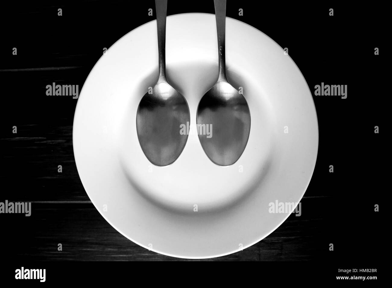 Spoons on plate, laughing face - Stock Image