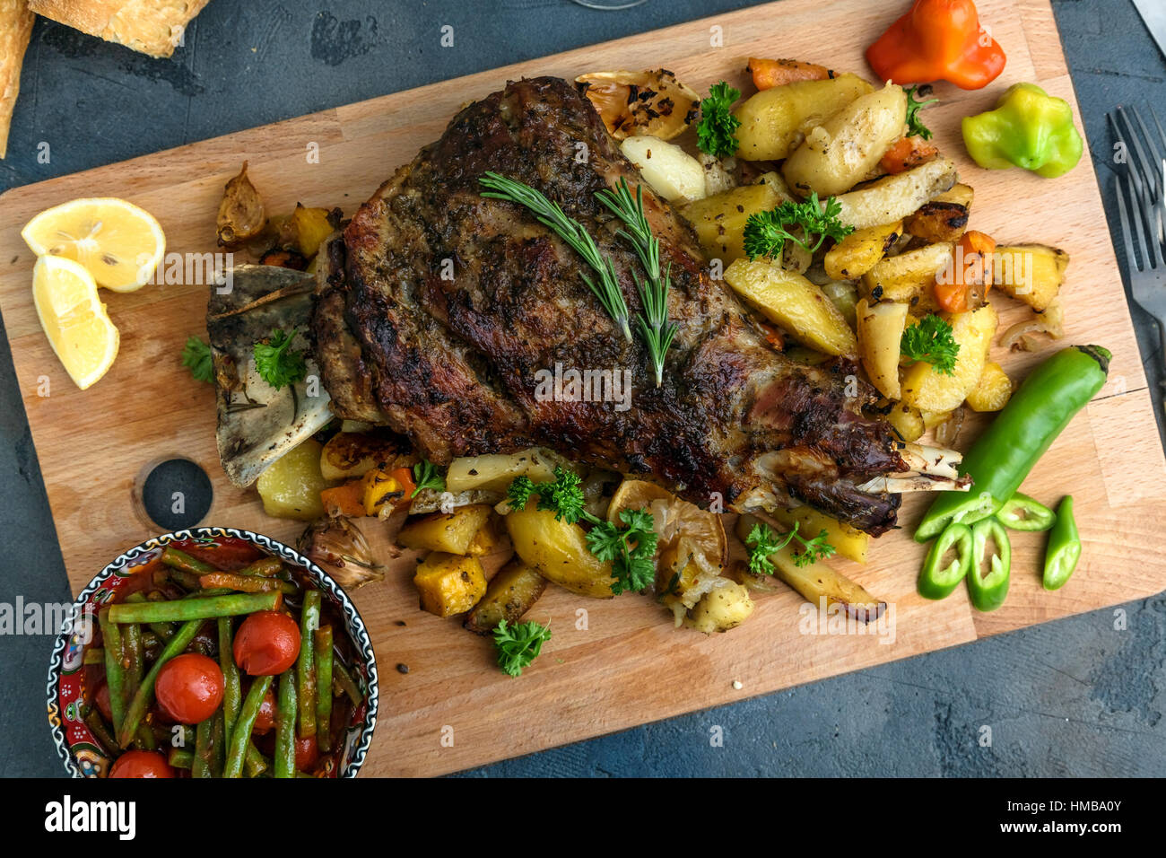 Roast shoulder of lamb on baked potato and carrots, wooden board, top view - Stock Image