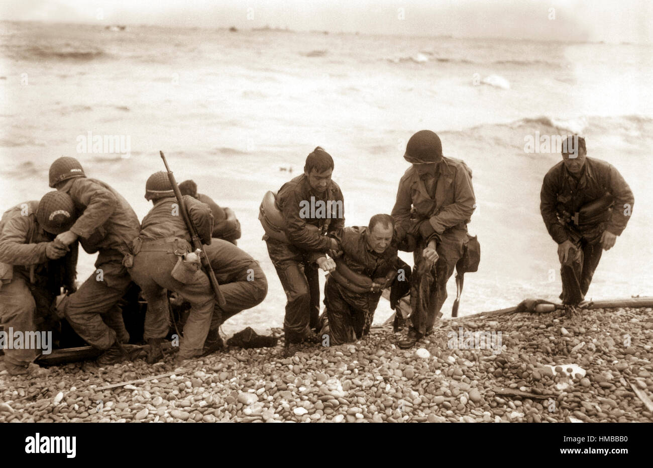 Members of an American landing party lend helping hands to others whose landing craft was sunk by enemy action off - Stock Image